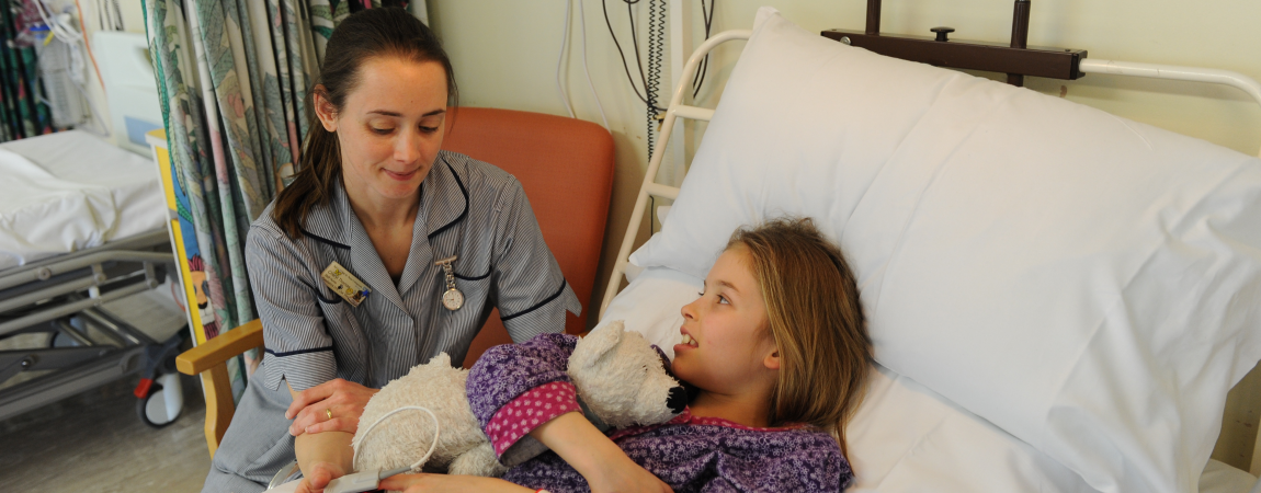 A member of the clinical team with a young patient - Click here to find out more about Visiting Information