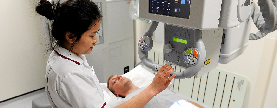 Clinical staff member performing radiology scan on patient