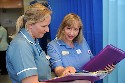 Two members of the clinical team with patient records